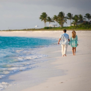 Resort couple sunset beach walk